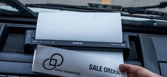 Mobilní tiskárna dokumentů Brother na palubní desce vozidla tiskne dokument
