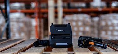 Imprimantă mobilă RJ neagră pe rafturi în depozit, cutii, paleți, scaner portabil