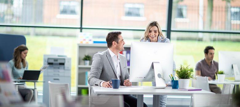 Muž sedí u stolního počítače a mluví s ženou s dlouhými blonďatými vlasy, lidé pracují na notebooku v pozadí, tiskárny, hrnky, rostliny a židle