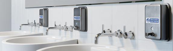 Tri umývadlá na toalete s P-touch značením na dávkovačoch mydla