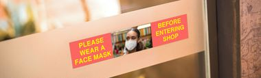 Nápis na dveřích obchodu s požadavkem, aby zákazníci nosili masku