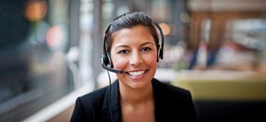 Žena se staženými tmavými vlasy a sluchátky s mikrofonem