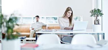 Kobieta siedzi przy biurku z laptopem, mężczyzna z tyłu na pomarańczowej kanapie, rośliny, zeszyty, białe krzesła, okno