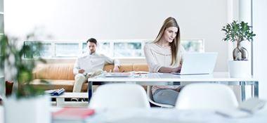 Žena sedí u stolu s notebookem, muž sedí vzadu na oranžové pohovce, rostliny, notebooky, bílé židle