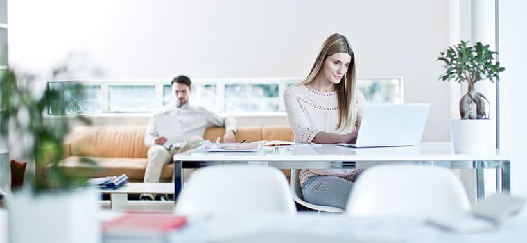 Nő ül az íróasztalnál laptop előtt, egy ember hátul ül a narancssárga kanapén, növények, notebookok, fehér székek, ablak