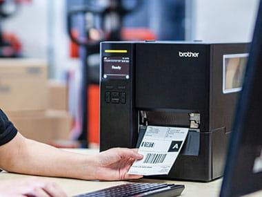 Mână care ia eticheta tipărită cu imprimanta industrială de etichete Brother