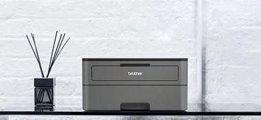Ciemnoszara drukarka laserowa monochromatyczna HL-2350DW na szklanym stole, obok stoi dyfuzor