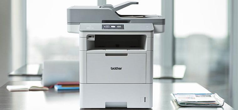 Monochromatická laserová podniková tiskárna MFC-L6900DW na stole v kanceláři