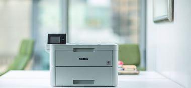 Laserová tiskárna Brother HL-L3270CDW na bílém stole v kanceláři, zelená židle v pozadí