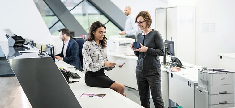 Dvě ženy hovoří v rušné kanceláři, multifunkční tiskárna na pozadí