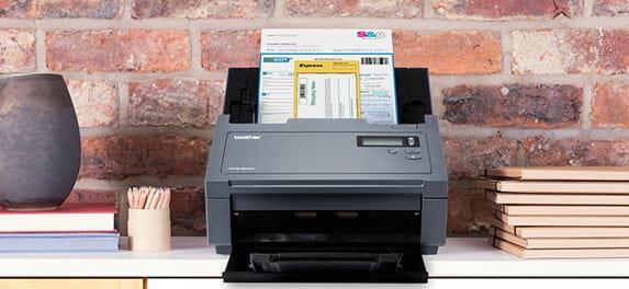 Profesionální skener Brother PDS-6000 snímá dokument na stole před cihlovou zdí