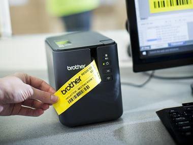 Drukarka etykiet P-touch P900W firmy Brother drukuje żółte etykiet przy pomocy komputera typu PC