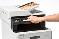 MFP colour laser with colour output and person pressing touchscreen