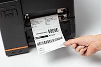 Prim plan cu imprimanta industrială de etichete Brother TJ, imprimând coduri de bare