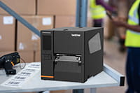 Индустриален етикетен принтер Brother TJ на работен плот с отпечатани етикети и баркод скенер в склад