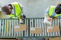 Dva zaměstnanci v reflexních vestách kontrolují štítky na hnědých krabicích
