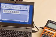 Imprimantă de etichete Brother PT-E550WNIVP conectată la un computer care rulează software-ul de proiectare a etichetelor P-touch Editor utilizând un cablu USB