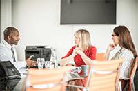 2 femei și un bărbat așezați la masă cu imprimanta Brother în fundal