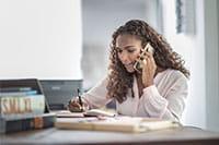 Ženska z dolgimi skodranimi rjavimi lasmi sedi za mizo in govori po telefonu