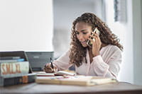 Жена в малък офис говори по телефона