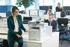 Žena-u-uredu-naslonjena-na-stol-s-DCP-L6600DW