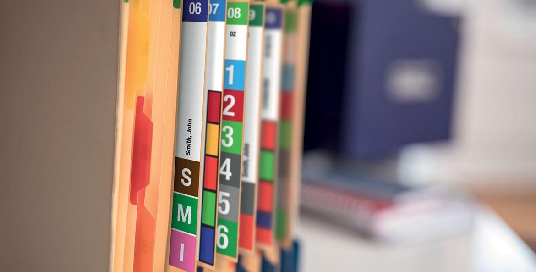 Etichete color imprimate pe un Brother VC-500W lipite pe dosare de birou