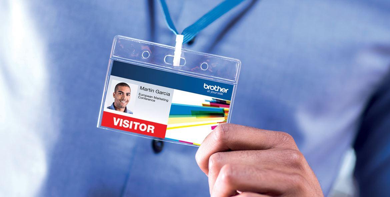 Moški v modri srajci drži v roki priponko za obiskovalce, natisnejno na tiskalnik barvnih nalepk Brother VC-500W