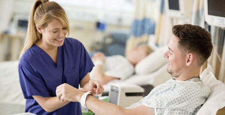 sestrička v nemocnici dávajúca náramok pacientovi na ruku