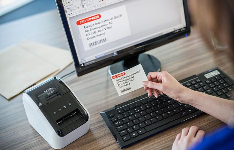 Brother QL tiskalnik poleg zaslona v pisarni, oseba, ki drži naslovno nalepko