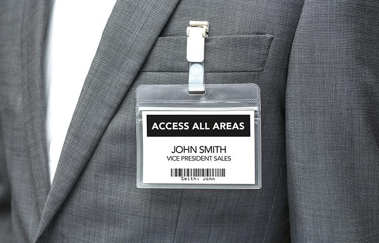 Priponka za obiskovalce, pritrjena na osebo, oblečeno v sivo jakno