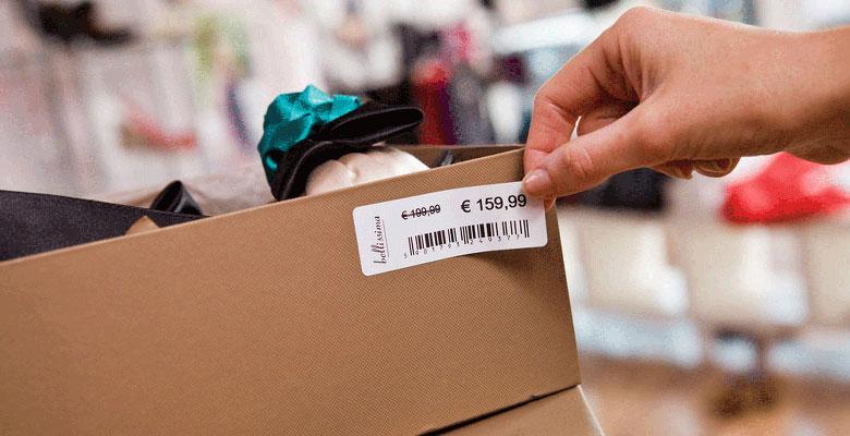 Ruka nanosi naljepnicu s crtičnim kodom na kutiju za cipele u trgovini