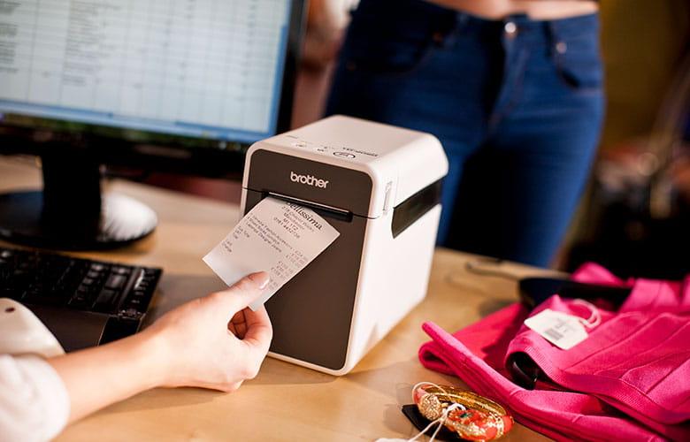 Odtržení účtenky ze stolní tiskárny štítků Brother TD-2 v obchodu