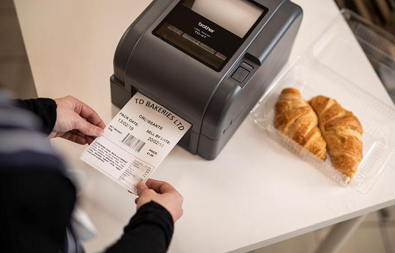 Stolní tiskárna Brother TD s termotransferovým tiskem generuje štítek na balení croissantů
