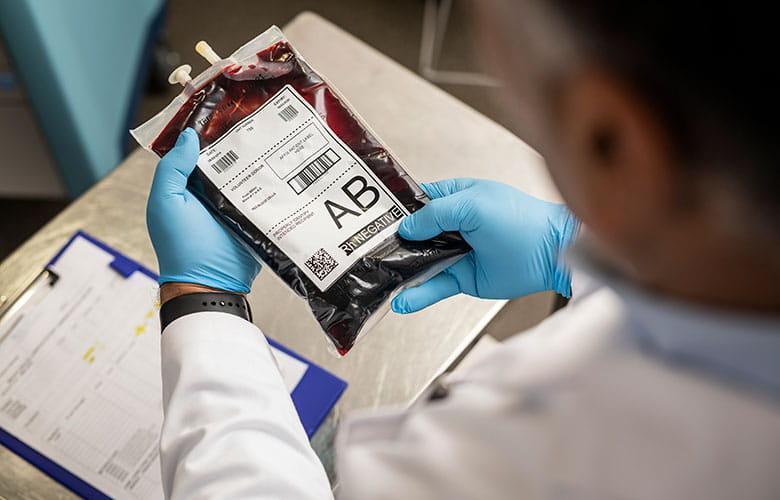 Doktor drží krevní vak označený štítkem