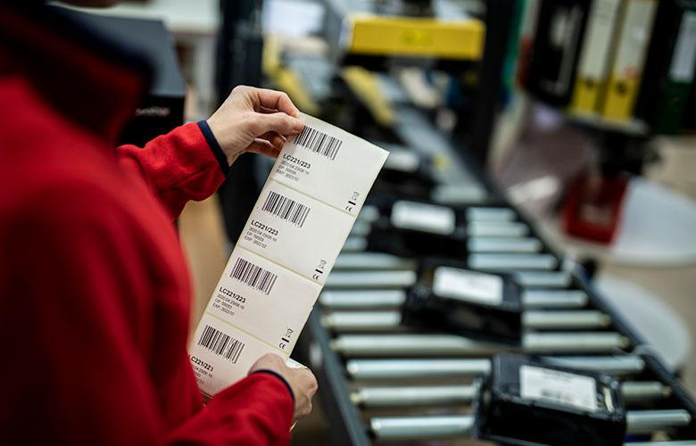 Etykiety produktowe trzymane przez pracownika przy linii produkcyjnej