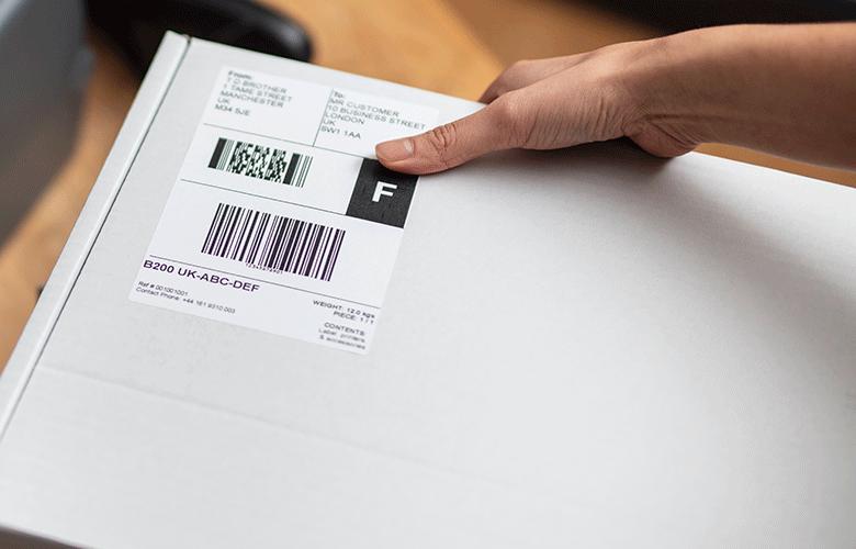 Bílý přepravní štítek lepený ručně na bílou krabici