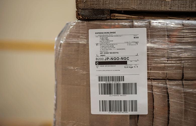 Primplan al unei etichete logistice albe lipita pe o cutie maro impachetata