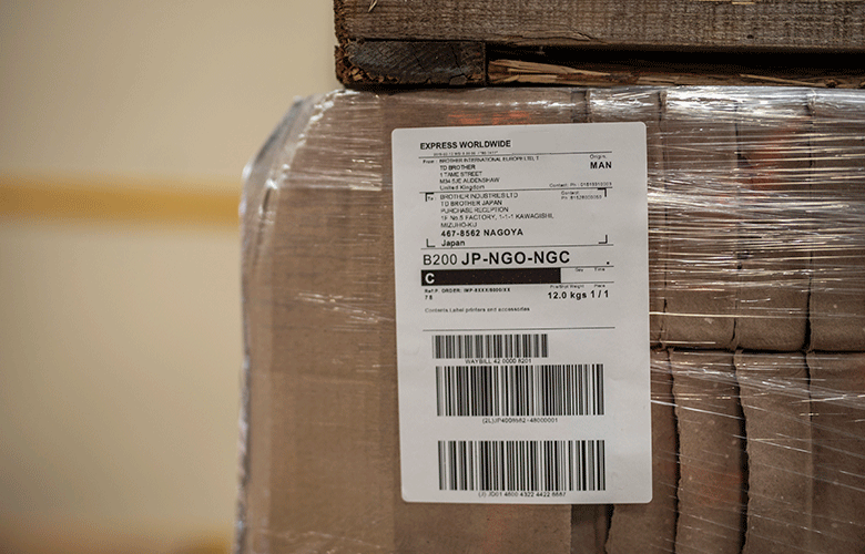biała etykieta wysyłkowa jest naklejona na brązowe pudełko