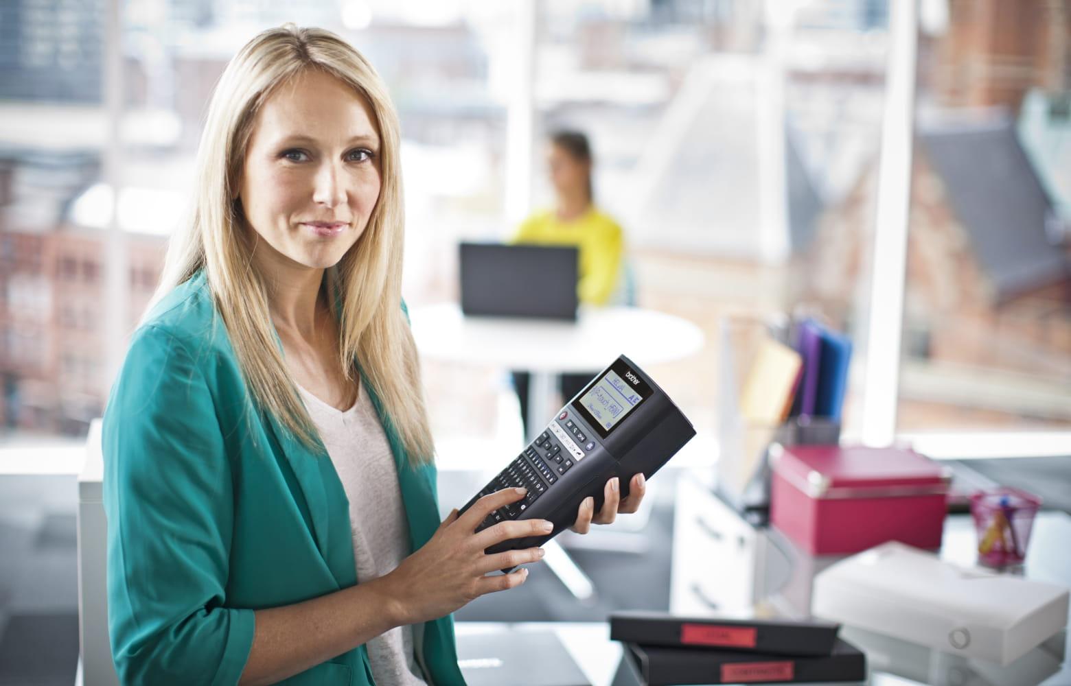 Upraviteljica objektov drži tiskalnik nalepk Brother P-touch, pripravljen za označevanje izdelkov po pisarni
