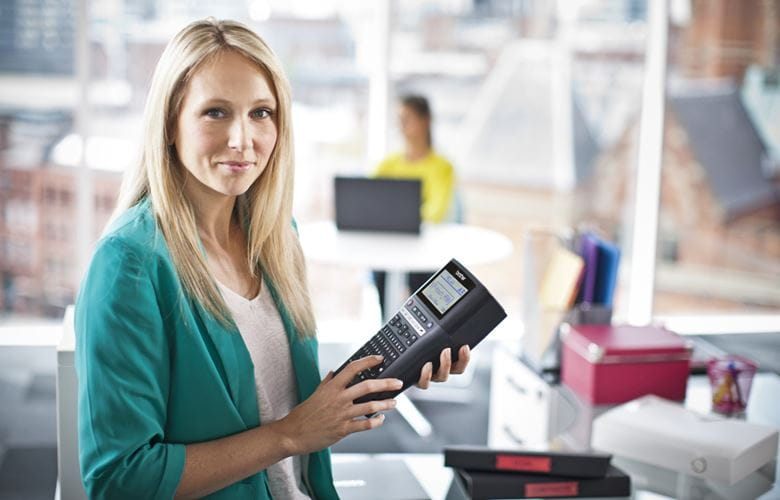 Női irodavezető, aki Brother P-touch címkenyomtatót tart a kezében az áru címkézéséhez az irodában