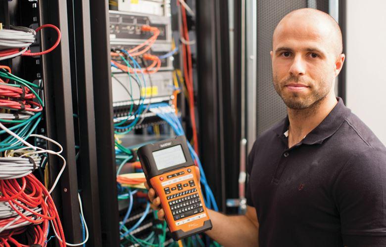 Мрежов техник стои пред подреден и маркиран мрежов шкаф, държи P-touch принтер