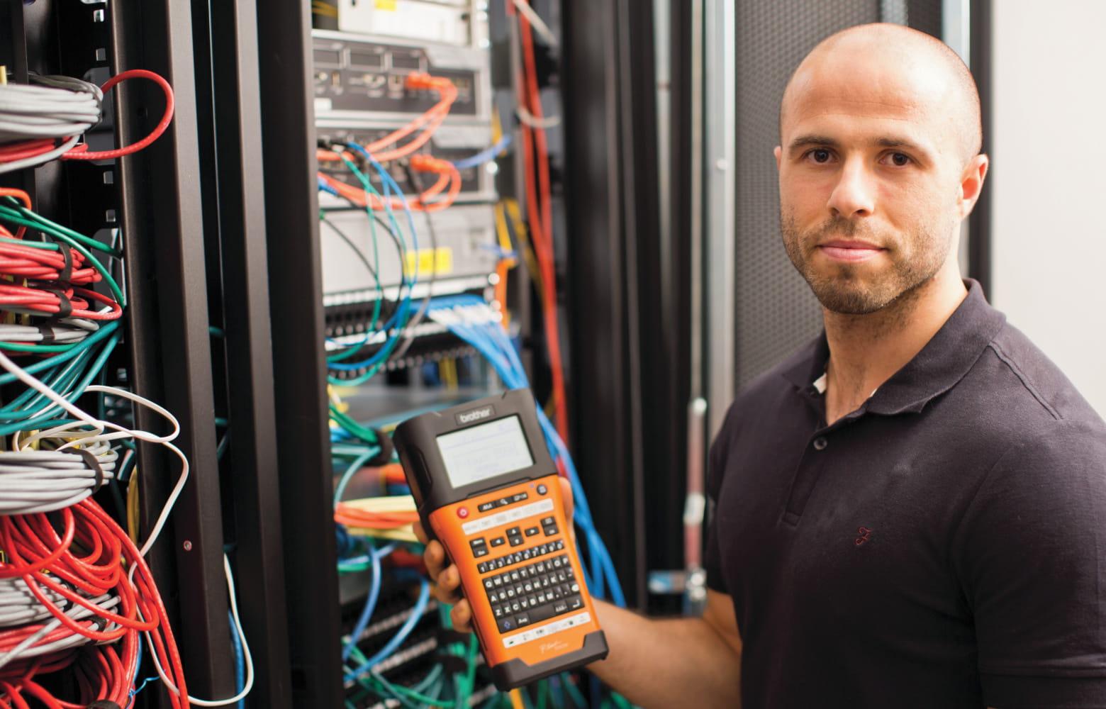tehničar stoji ispred uredno označenog mrežnog ormarića, dok drži P-touch pisač naljepnica