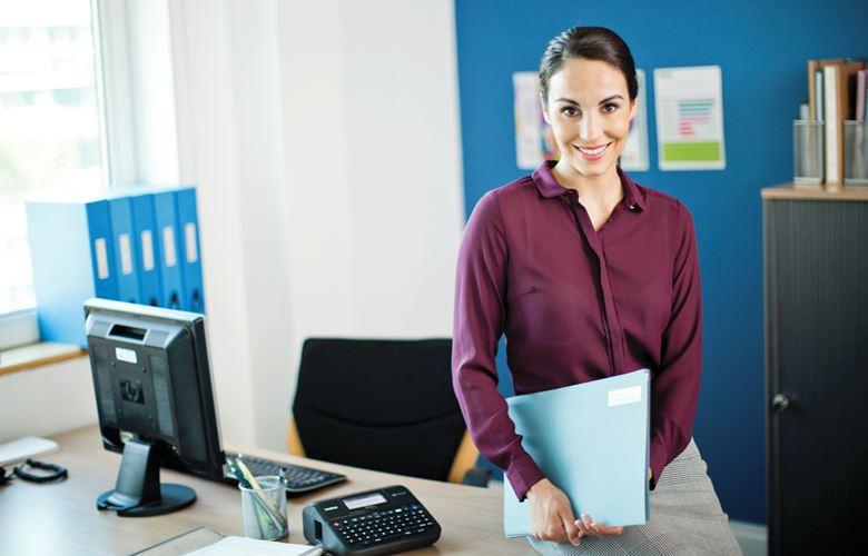 Pisarniška delavka poleg pisarniške mize z mapo z datotekami v roki, zraven računalnik in tiskalnik nalepk Brother P-touch