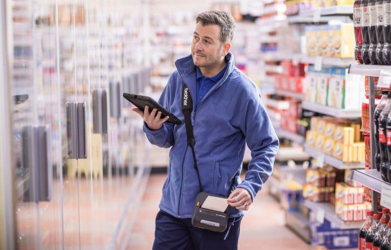 Doručovateľ v modrom pulóvri v supermarkete drží tablet a na ramene má tlačiareň Brother RJ