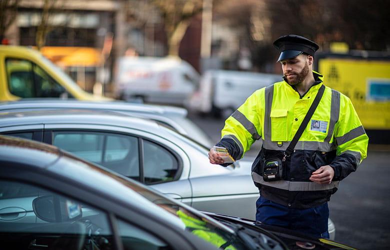 Policista umísťující lístek na auto na parkovišti