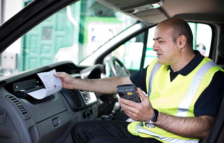 Muž v reflexnej veste vo vnútri vozidla tlačí list papiera A4 z tlačiarne Brother PJ