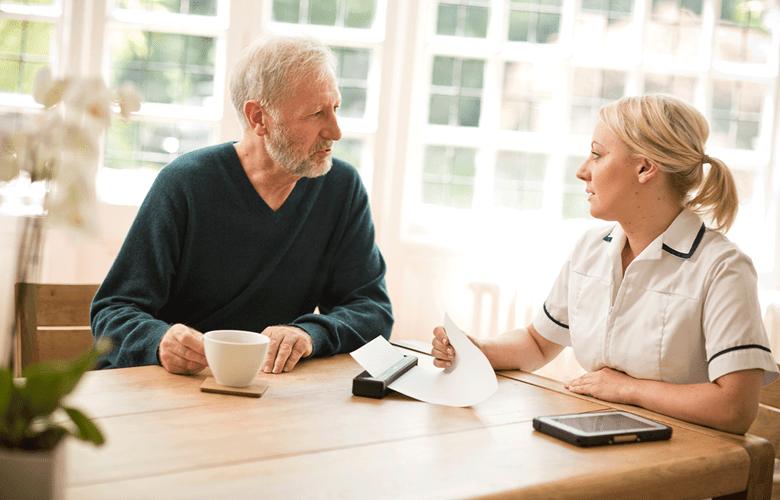 Възрастен мъж и здравен служител стоят на маса със мобилен принтери серия PJ