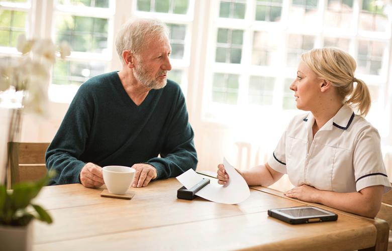 Mężczyzna i kobieta z opieki zdrowotnej siedzą przy drewnianym stole, drukarka PJ drukuje dokument