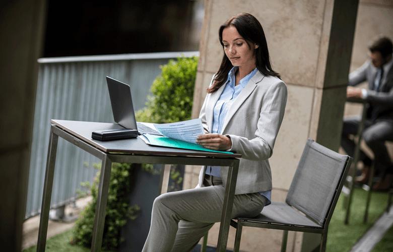 Ženska v belem kostimu sedi za mizo na prostem, tiskalnik PJ, dokumenti, prenosni računalnik