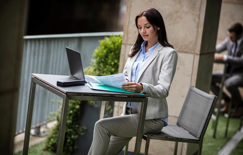 Žena u stolu s PJ tiskárnou a notebookem